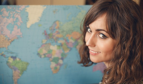 Woman with World Map in Background Looking over Shoulder at Camera as if Planning a Trip